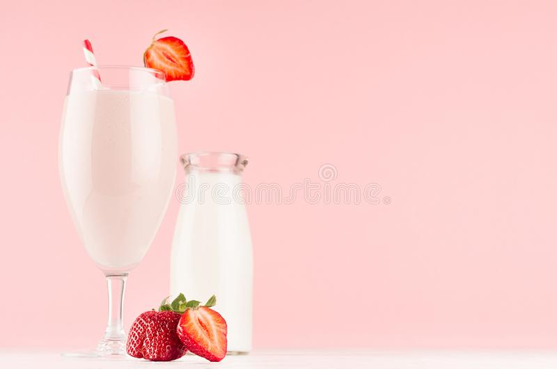Cooking of spring fresh pink milkshake with strawberry, bootle of milk on soft pink background, copy space. Cooking of spring fresh pink milkshake with stock images