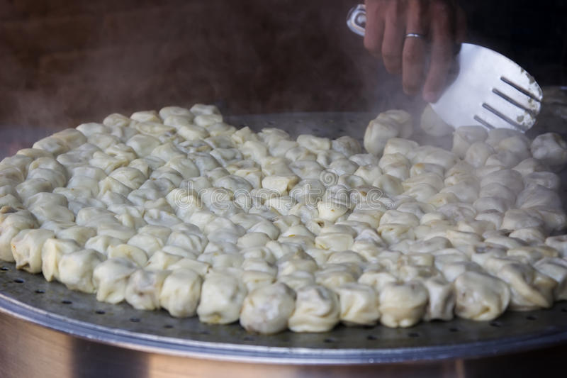 Cooking steamed traditional Nepalese momos in the street kitche royalty free stock images