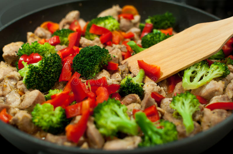 Cooking stew. Cooking dinner - closeup shot of meat, broccoli and paprika on a frying pan royalty free stock photography