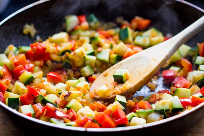 Cooking stew ratatouille from vegetables in frying pan. Delicious vegetarian french dish royalty free stock images