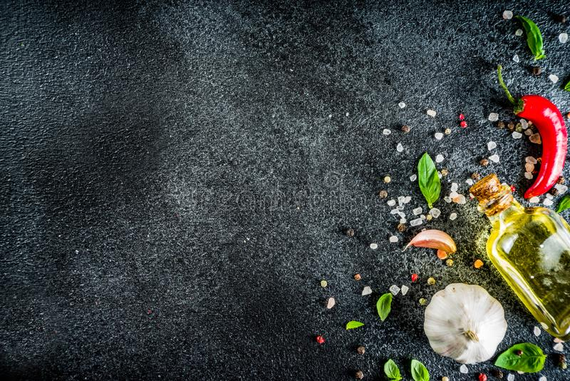 Cooking stone concrete background with spices. Cooking food stone concrete background with spices, olive oil, garlic, onion, pepper, herbs, basil. Top view copy royalty free stock images