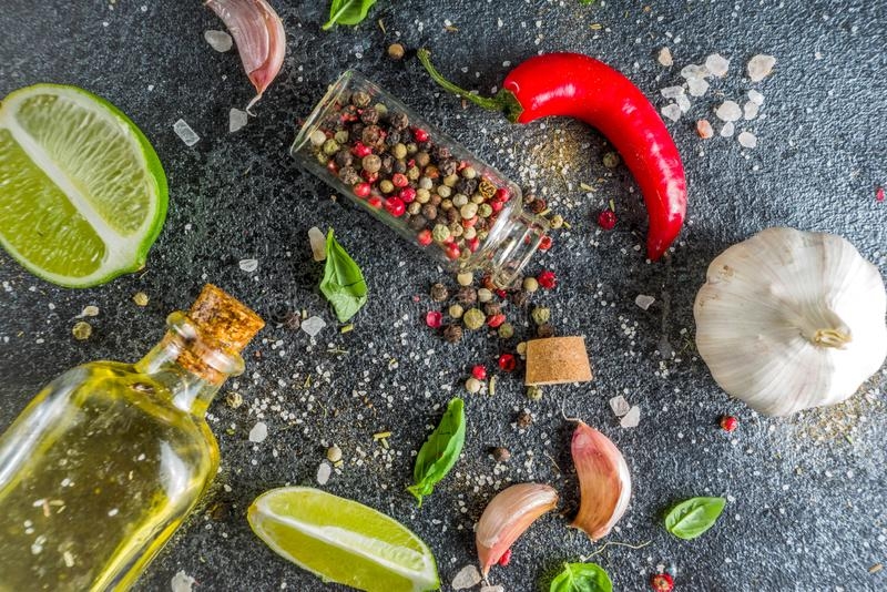 Cooking stone concrete background with spices. Cooking food stone concrete background with spices, olive oil, garlic, onion, pepper, herbs, basil. Top view copy stock photo