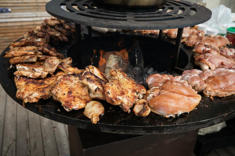 Cooking Street Food - Meat And Poultry. Are Fried On A Round Cast-Iron Brazier With An Open Fire In The Center stock photo