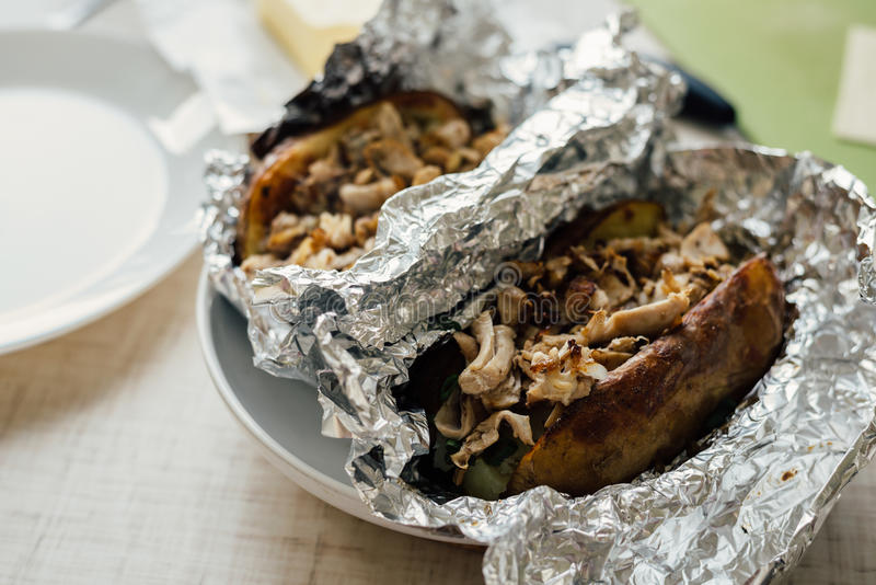 Cooking stuffed baked potato. Cooking baked potato in jacket with butter, chicken and green onion royalty free stock photo