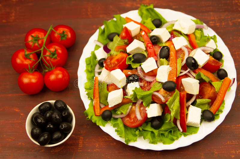 Cooking summer Greek salad on wooden background stock photos