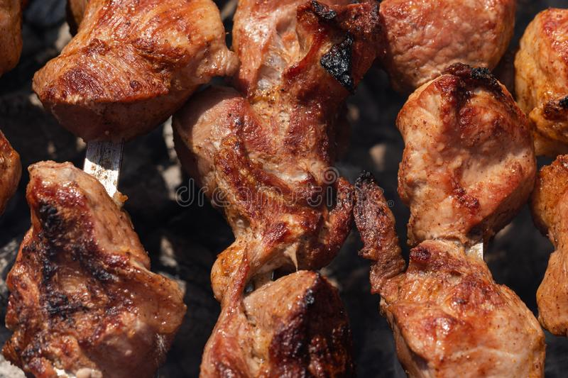 Cooking during summer picnic - appetizing juicy pork shish kebabs on metal skewers on charcoal grill stock photography