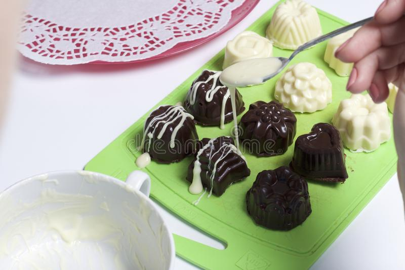Cooking sweets with coconut and condensed milk. In a glaze of white and black chocolate stock image