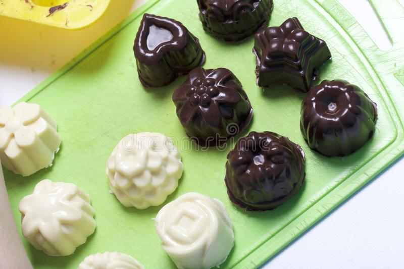 Cooking sweets with coconut and condensed milk. In a glaze of white and black chocolate.  royalty free stock photo