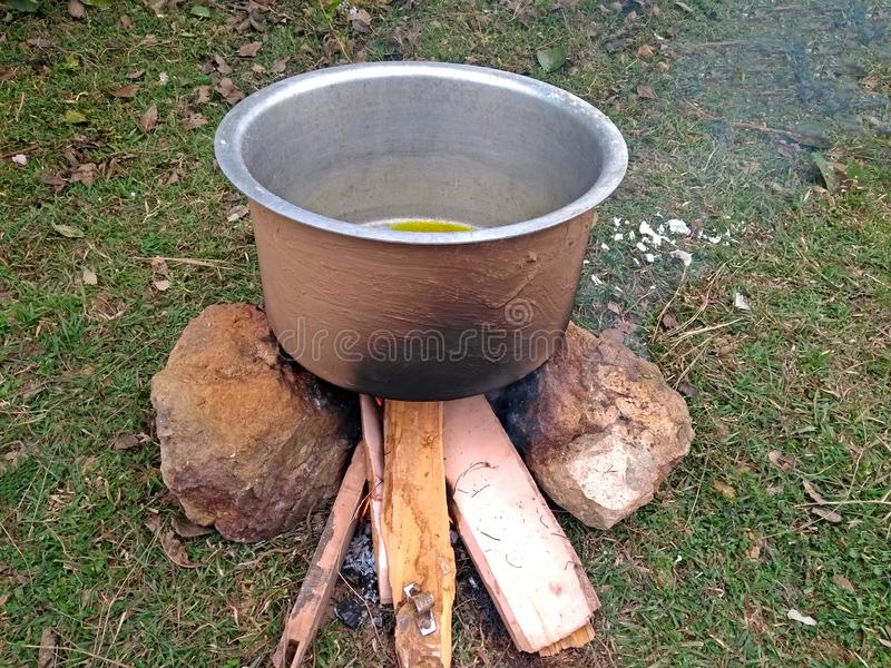 Cooking tasty delicious indian food item during a picnic or outdoor camp using stone made firewood oven and aluminium pot at an op stock photo