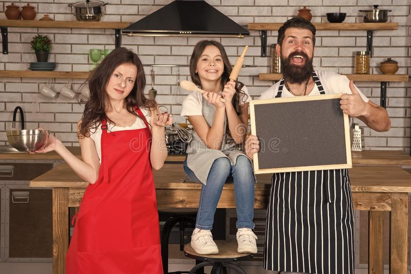 Cooking together. Family mom dad and daughter wear aprons stand in kitchen. Cooking food concept. Prepare delicious meal. Breakfast time. Family having fun stock image