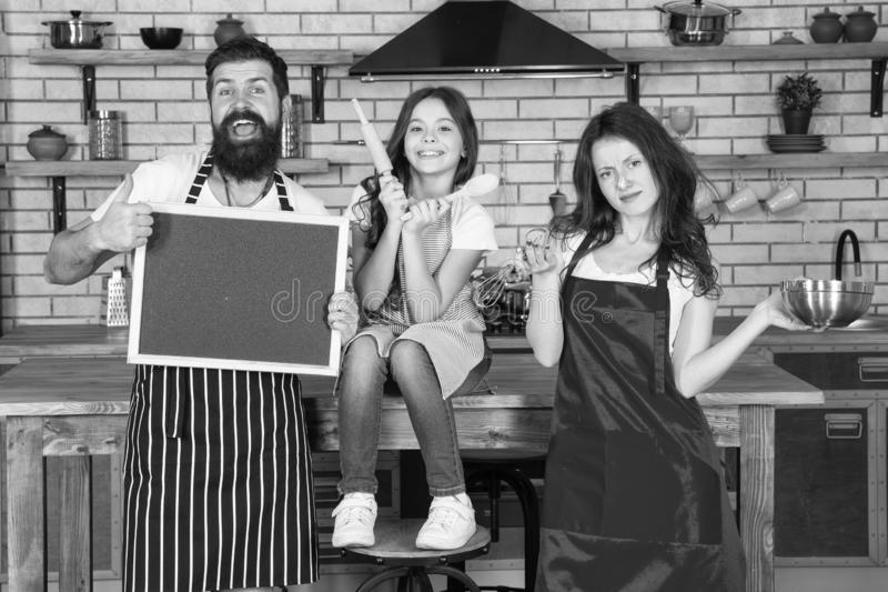 Cooking together. Family mom dad and daughter wear aprons stand in kitchen. Cooking food concept. Prepare delicious meal. Breakfast time. Family having fun stock photography