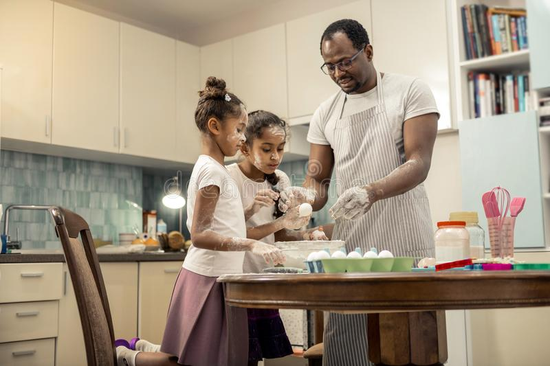 Father and daughters standing near table in kitchen cooking together. Cooking together. Father and daughters standing near table in the kitchen cooking pie for stock photos
