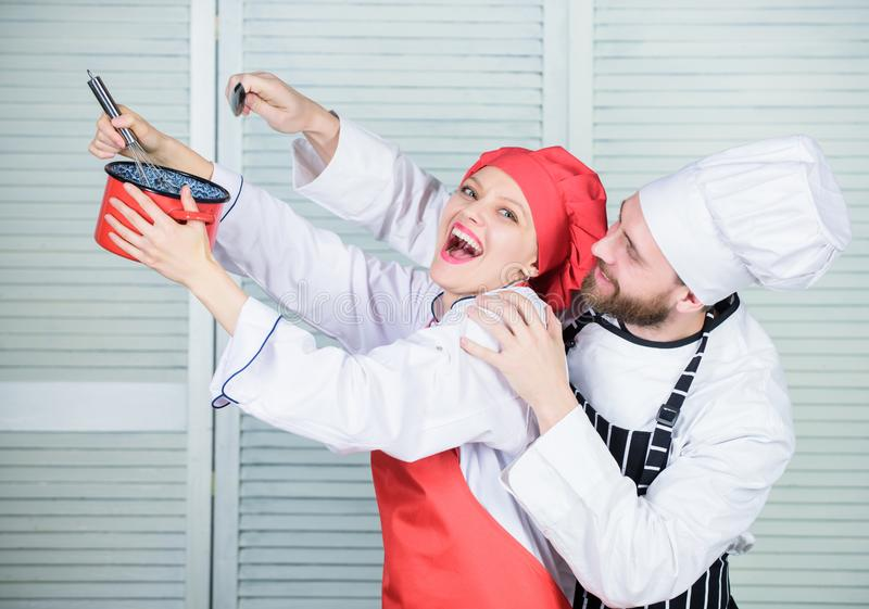 Cooking together is more fun. Let my try taste. Couple having fun while whipping cream. Cooking healthy meal. Woman and royalty free stock photos