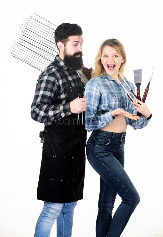 Cooking together. Tools for roasting meat outdoors. Picnic and barbecue. Bearded hipster and girl ready for barbecue royalty free stock image