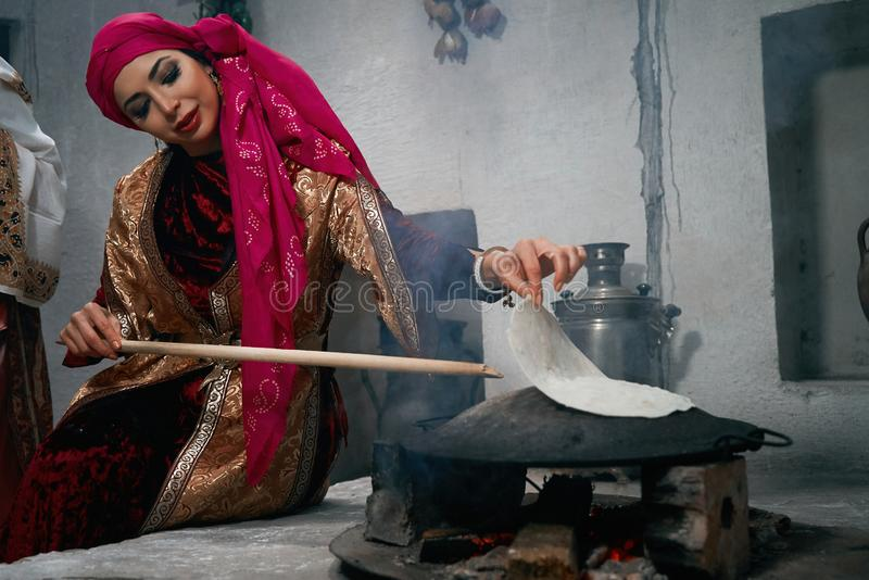 Woman preparing or making borek or bread dough on fire. Cooking traditional Turkish borek, pide, pita or yufka bread. Traditional Turkish food. Woman preparing royalty free stock photos