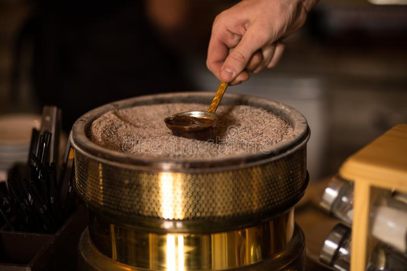 Cooking Turkish coffee in sand and a cezve. Turkish coffeee is a traditional hot drink. In Turkey royalty free stock image