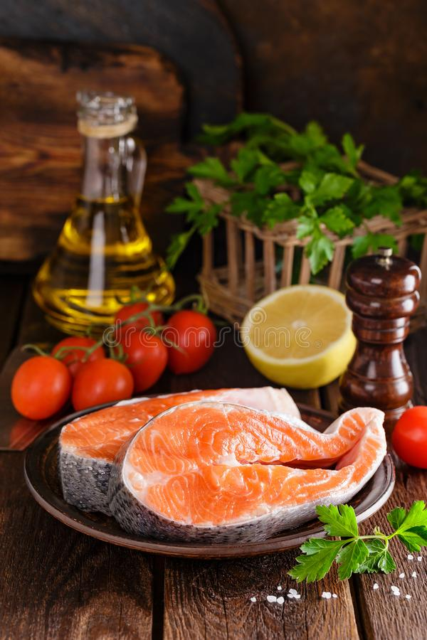 Cooking two fresh raw salmon fish steaks on wooden rustic table stock photos