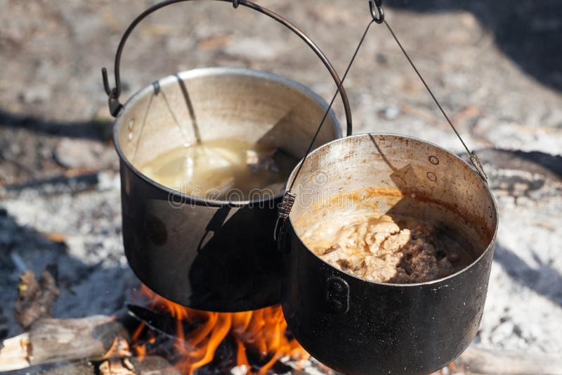 Cooking in two sooty old pots on bonfire at sunny summer day royalty free stock photo