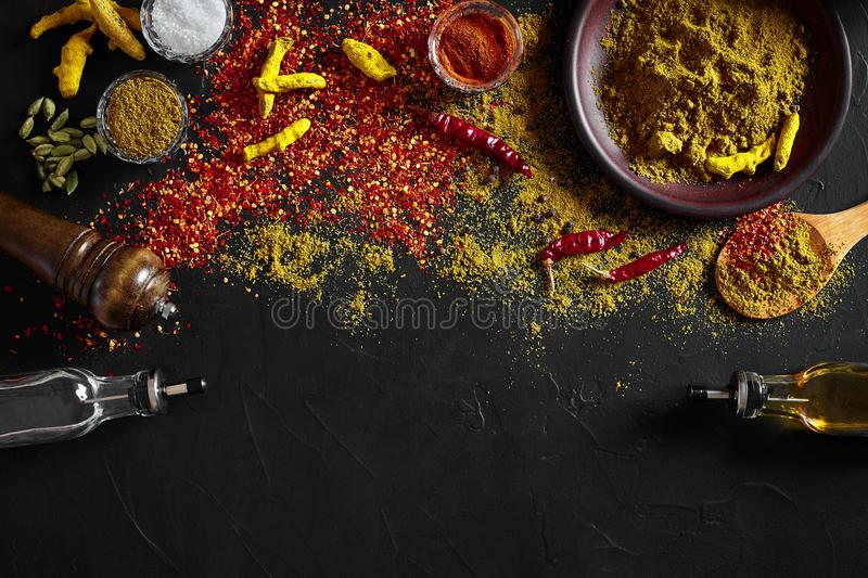 Cooking using fresh ground spices with big and small bowls of spice on a black table with powder spillage on its surface royalty free stock photos