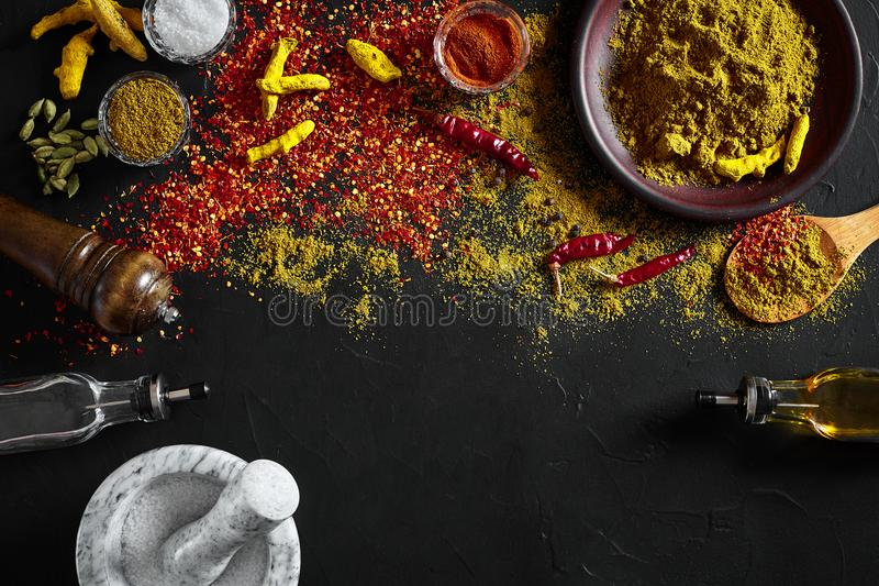 Cooking using fresh ground spices with mortar and small bowls of spice on a black table with powder spillage on its royalty free stock photo