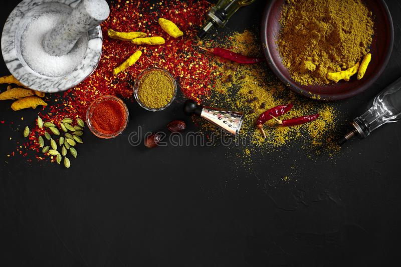 Cooking using fresh ground spices with mortar and small bowls of spice on a black table with powder spillage on its stock photo