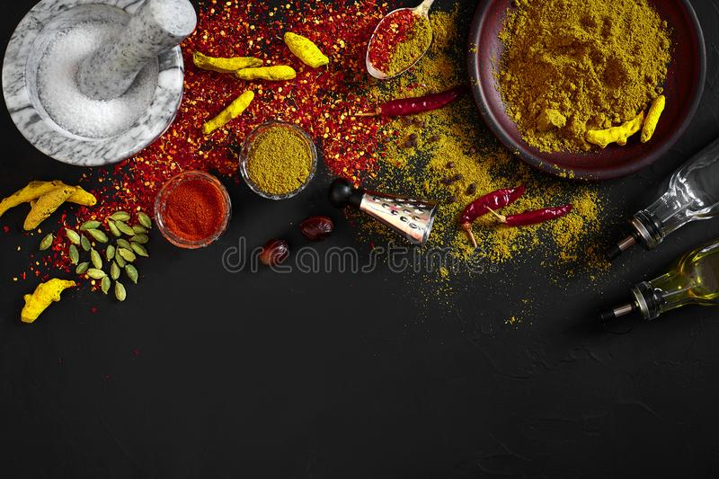 Cooking using fresh ground spices with mortar and small bowls of spice on a black table with powder spillage on its royalty free stock image