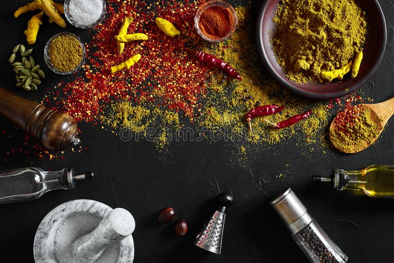 Cooking using fresh ground spices with mortar and small bowls of spice on a black table with powder spillage on its stock image