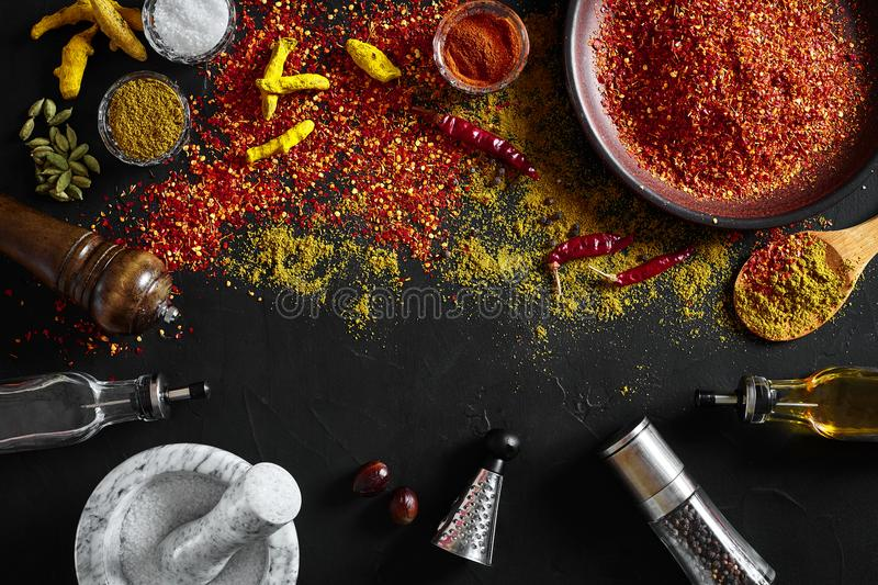 Cooking using fresh ground spices with mortar and small bowls of spice on a black table with powder spillage on its stock images