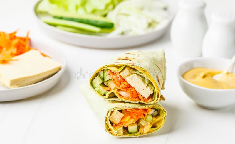 Cooking vegan tofu wraps with cashew cheese sauce and vegetables, white background royalty free stock images