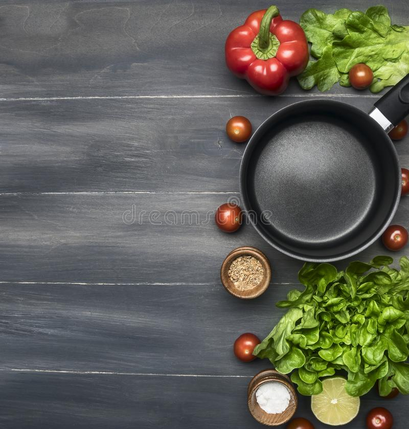 Cooking a vegetarian dinner, red and yellow bell peppers, salad, wooden spoon, cherry tomatoes, condiments,lime, black cooking pot royalty free stock photo