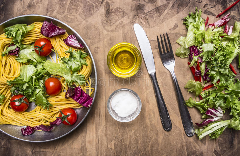 Cooking vegetarian pasta with salad and vegetables, oil and salt for food appliances royalty free stock images