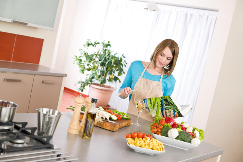 Cooking - Woman Reading Cookbook In Kitchen Stock Photo