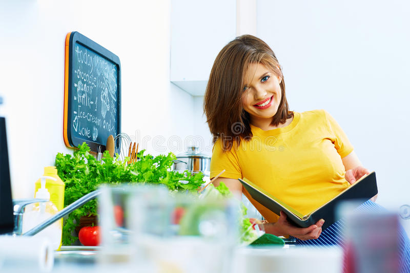 Cooking woman standing in kitchen, reed recipe from menu. Book stock images