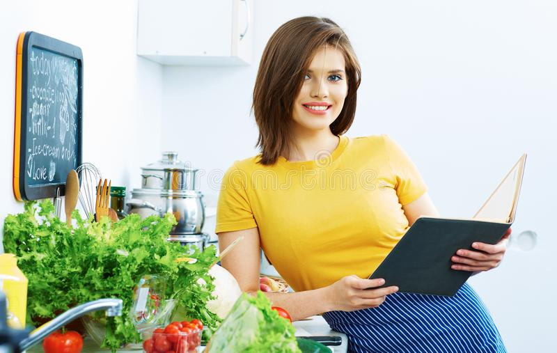 Cooking woman standing in kitchen, reed recipe from menu. Book royalty free stock images