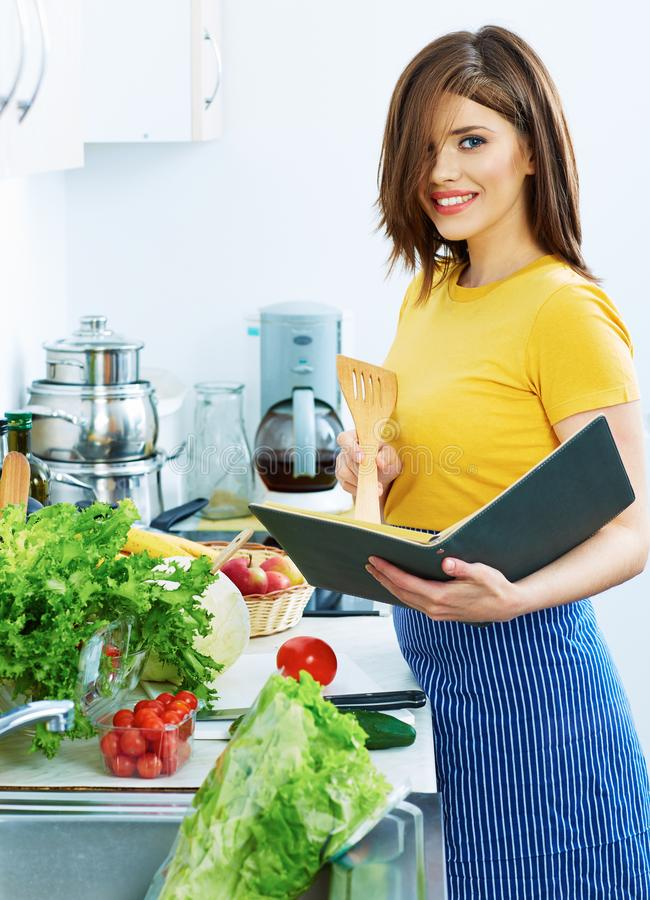 Cooking woman standing in kitchen, reed recipe from menu. Book royalty free stock image