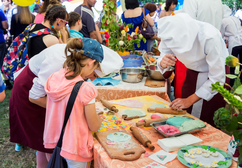 Cooking workshop on charity Family Festival. Zaporizhia/Ukraine- June 5, 2016: girl participating in pastry cooking workshop, learning to make colorful paste stock photos