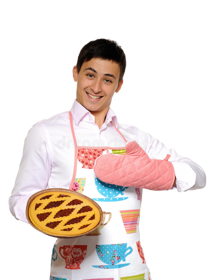 Cooking. Young man in apron baked tasty pie stock image