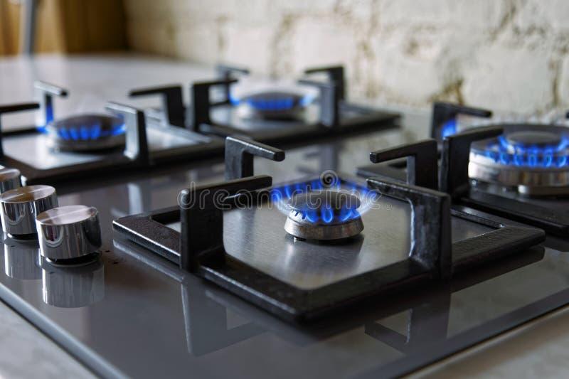 Cooktop mit brennendem Gaskocher Gaskocher mit blauen Flammen Abgetöntes Foto stockfotos