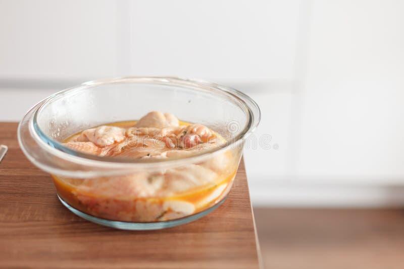 Cookware de cristal con un pollo adobado imagen de archivo