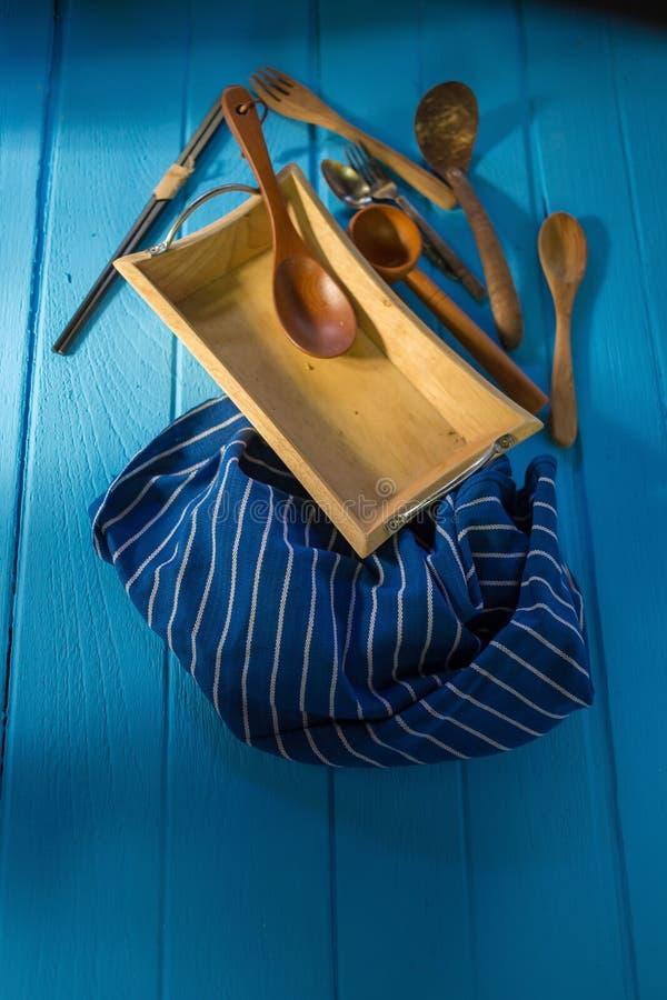 cookware de madera sobre fondo de madera azul de la tabla imagenes de archivo