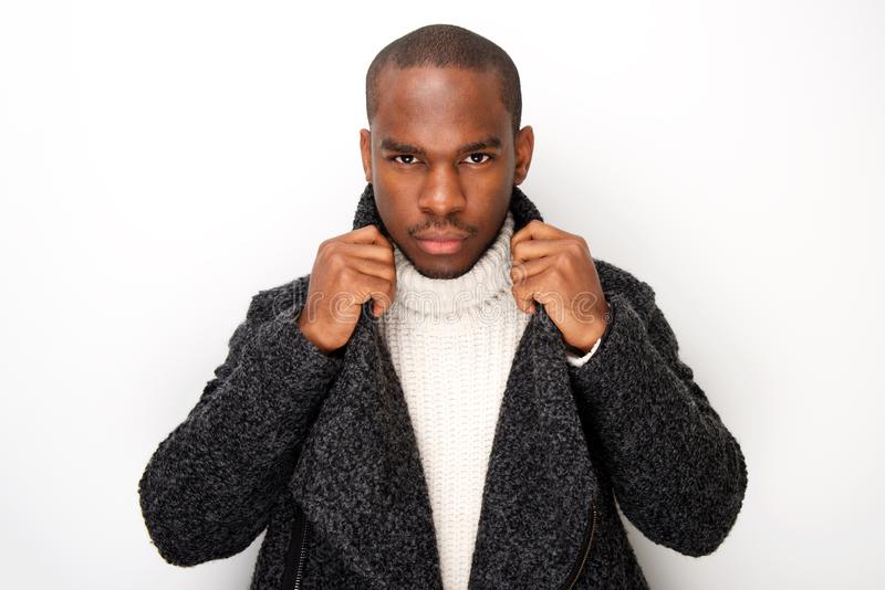 Cool african american male fashion model with coat against isolated white background royalty free stock image
