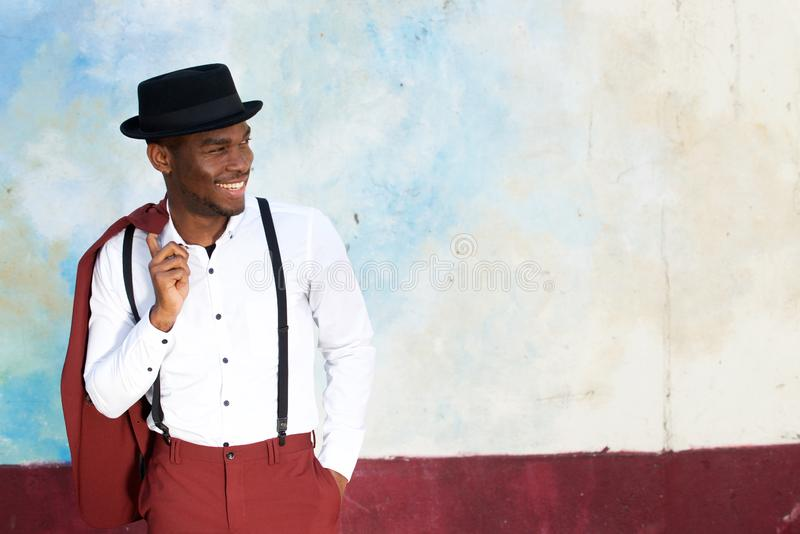 Cool african american male fashion model smiling with vintage suit, suspenders and hat by wall royalty free stock images