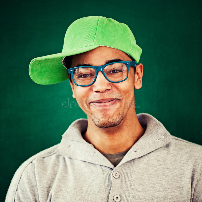 Cool African Rapper. Smiling African rapper wearing a cap and blue glasses stock image