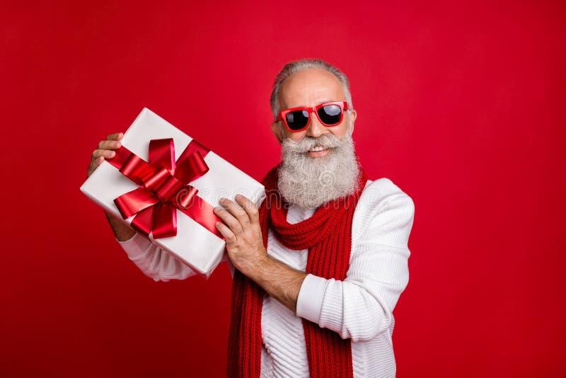 Cool aged santa, als man, kwam nieuwjaar bijeen met grote cadeautjes op zonescherm, van brei-jumper geïsoleerde rode achtergrond royalty-vrije stock fotografie