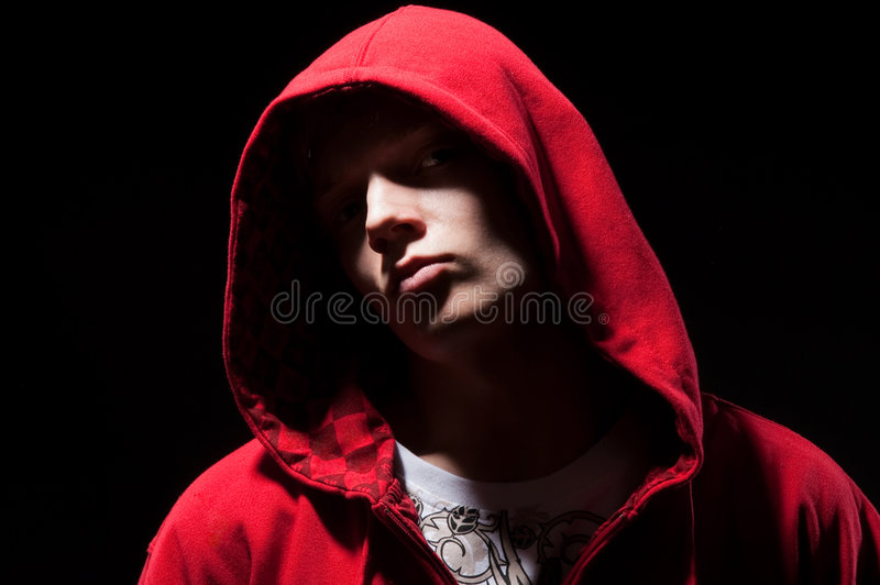 Cool b-boy in red jacket. Against black background stock photography