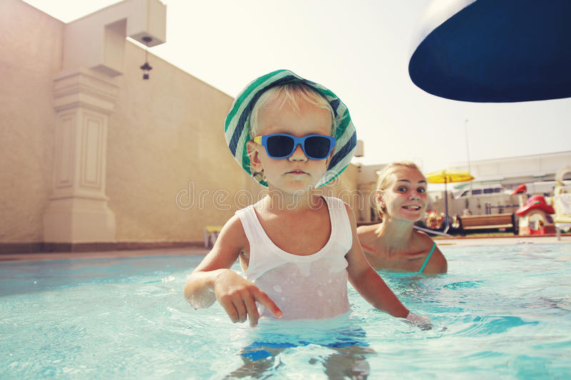 Cool baby boy in the swimming pool. Cool baby boy with mother in the swimming pool royalty free stock image