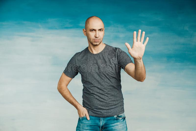 A cool bald man looks at the camera and shows open palm and five fingers, stock photo