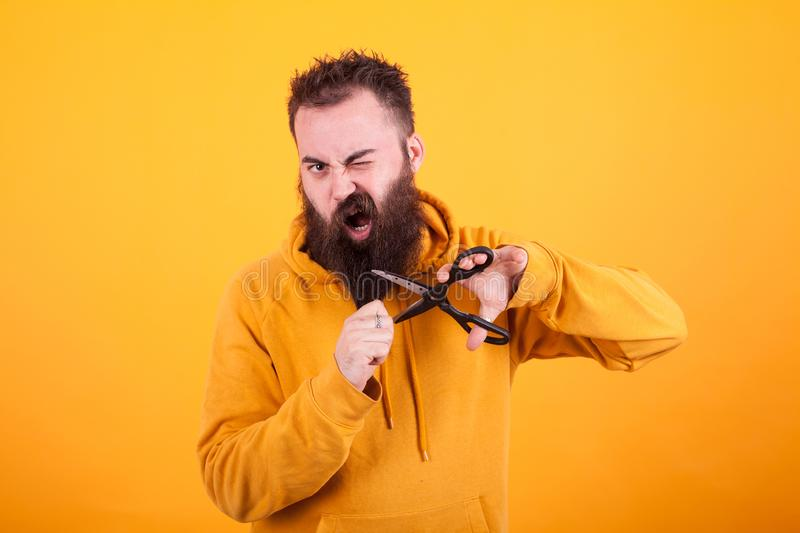 Cool bearded man looking terrified while cutting his beard over yellow background stock photography