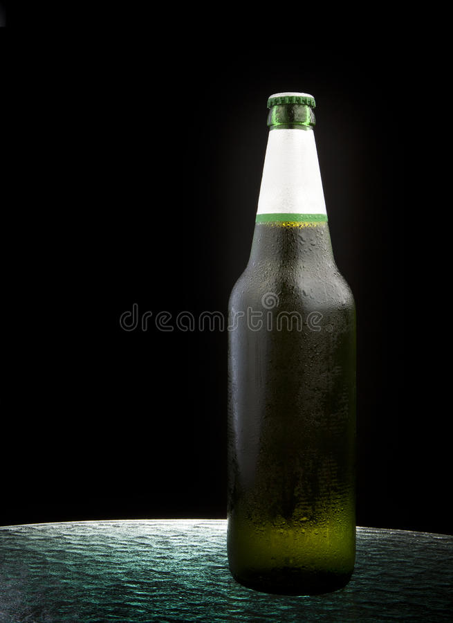 Cool beer bottle on table royalty free stock photo