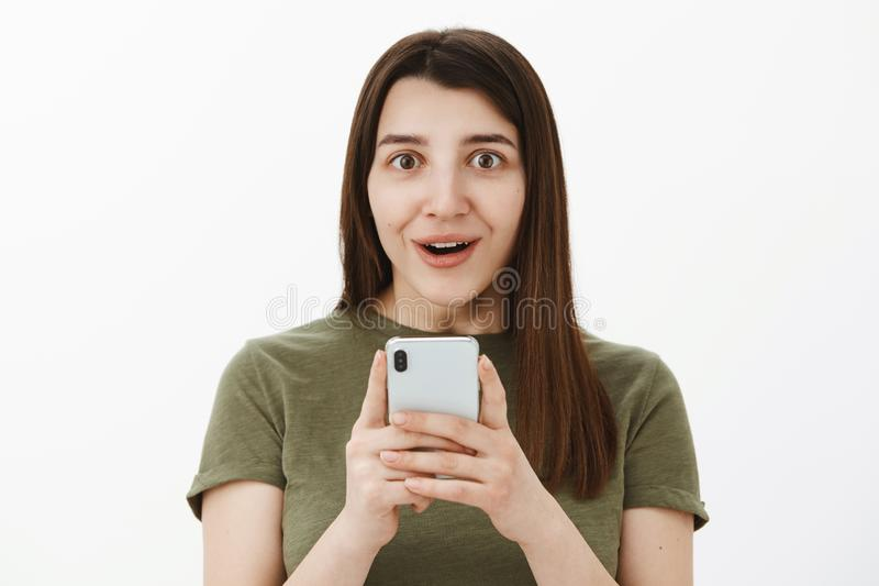 So cool best phone ever. Portrait of impressed and fascinated happy speechless brunette in 20s holding smartphone and stock photo